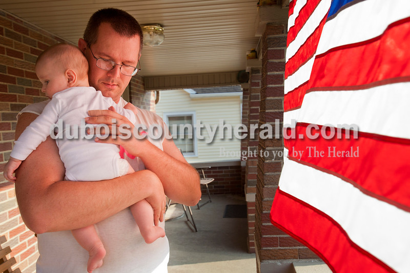 Rachel Mummey/The Herald<br /> Officer Mike Stallman of Jasper held his four-month old baby girl, Clara on the front porch of his home on Tuesday evening. He and his wife, Autumn, took Clara in for her four-month shots earlier in the day and got the okay from the doctor to begin feeding Clara cereal. Autumn was out to pick up the baby food, while dad and baby spent the evening enjoying the weather.