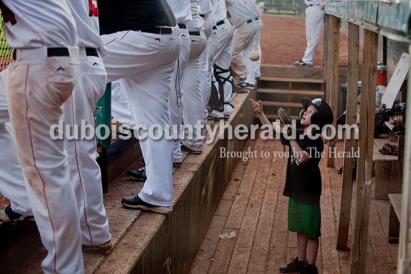 Brooke Stevens/The Herald<br /> Bat boy Carson Niehaus of Holland, 8, threw a baseball in Southridge's dugout during Saturday afternoons game against Southport in Huntingburg.