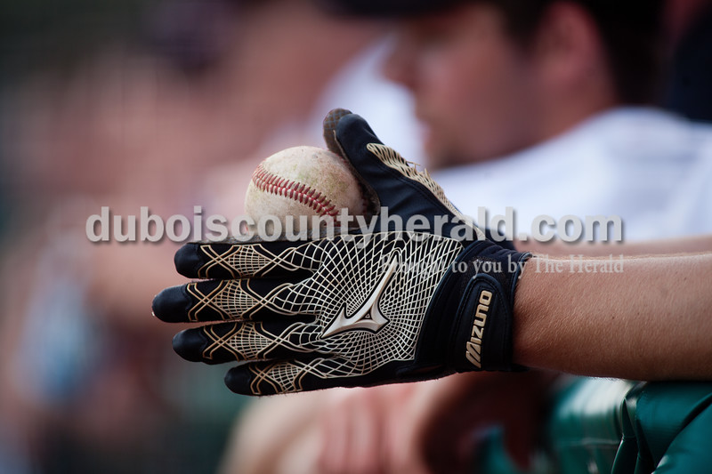 Brooke Stevens/The Herald<br /> Southridge's Ben Weber held a baseball in the dugout during Saturday afternoons game against Southport in Huntingburg.