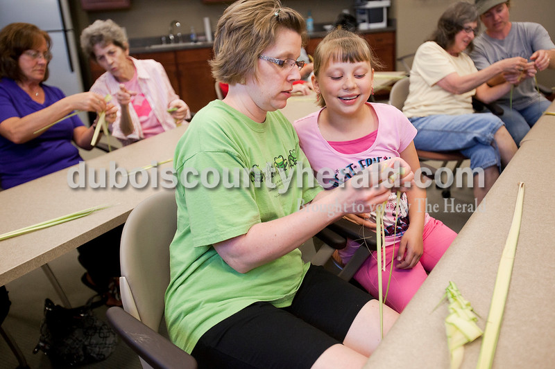 Rachel Mummey/The Herald<br /> Amy Lindauer of St. Henry helps her daughter, Abby, 9, how to braid palm leaves at Ferdinand Public Library on Monday, April 2, 2012 while, in background from left to right, Jeannie Wendholt of Jasper, Rita Kunkler of St. Meinrad, Miriam Ash and Tammy Haug, both of Ferdiand, work on their own. The event was sponsored by Friends of the Ferdinand Public Library and it was their second year holding the event.