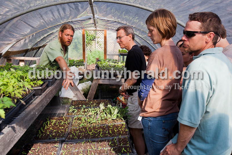 Rachel Mummey/The Herald<br /> Michael Hicks of Jasper showed Dave Beachy of Paoli, Grendlyn and Jon Cannon of Dubois and others attendees various plants housed in the greenhouse in his backyard. Hicks moderated a session on the basics of organic gardening which covered topics including garden design, soil awareness and plant selection.