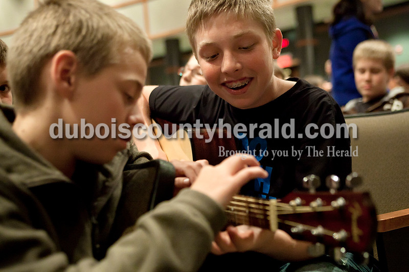 "Dave Weatherwax/The Herald<br /> Jasper Middle School seventh-grader Tad Reinsch, left, showed classmate Adam Hedinger where to place his fingers on the guitar to play the Deep Purple song ""Smoke on the Water"" on Thursday afternoon in the school's auditorium. The two were waiting for their turn to perform in the ""American Rock Idol"" in which a group from each of the 10 seventh-grade science classes performed a song they wrote about the topic of soil and weathering or rocks and minerals. Reinsch, Hedinger and another member of their group, Brandon Wildman, peformed a song they wrote about soil and weathering to the tune of Don McLean's ""American Pie."""