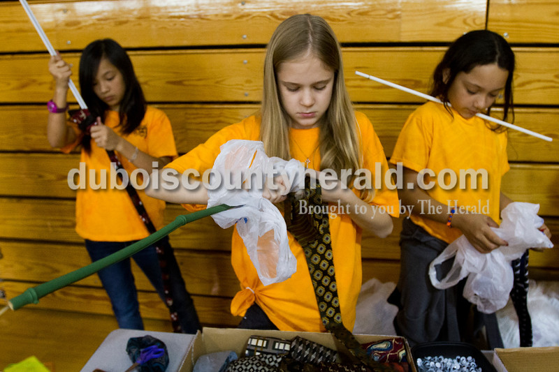 Brooke Stevens/The Herald<br /> Tenth Street Elementary fifth-graders, from left, Jolie Doan, Sydni Wiseman and Star Gonzalez, all of Jasper, stuffed ties with plastic bags to make snakes during the second annual fifth grade art fair Thursday afternoon at 10th Street School's gymnasium. Students designed craft project to sell or to teach others how to make them.