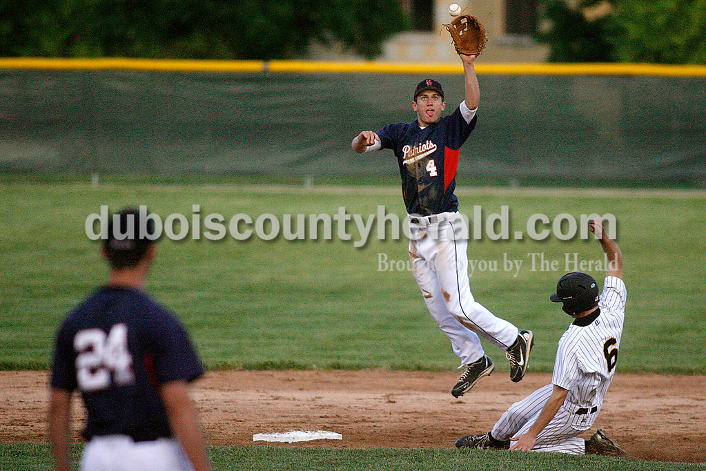Rachel Mummey/The Herald<br /> Heritage Hills' Damon Wahl leapt into the air for the ball as Jasper's Devon Traylor slid into second plate during the game at Ruxer Field on Monday evening.