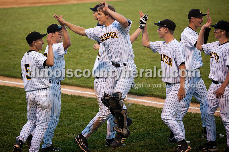 Rachel Mummey/The Herald<br /> Jasper's catcher Logan Hettinger jumped to give his teammates Jordan Haas and Jesse Schmitt, high fives with teammates Ben Mundy, Karson Nixon and others after beating Heritage Hills at Ruxer Field on Monday evening.