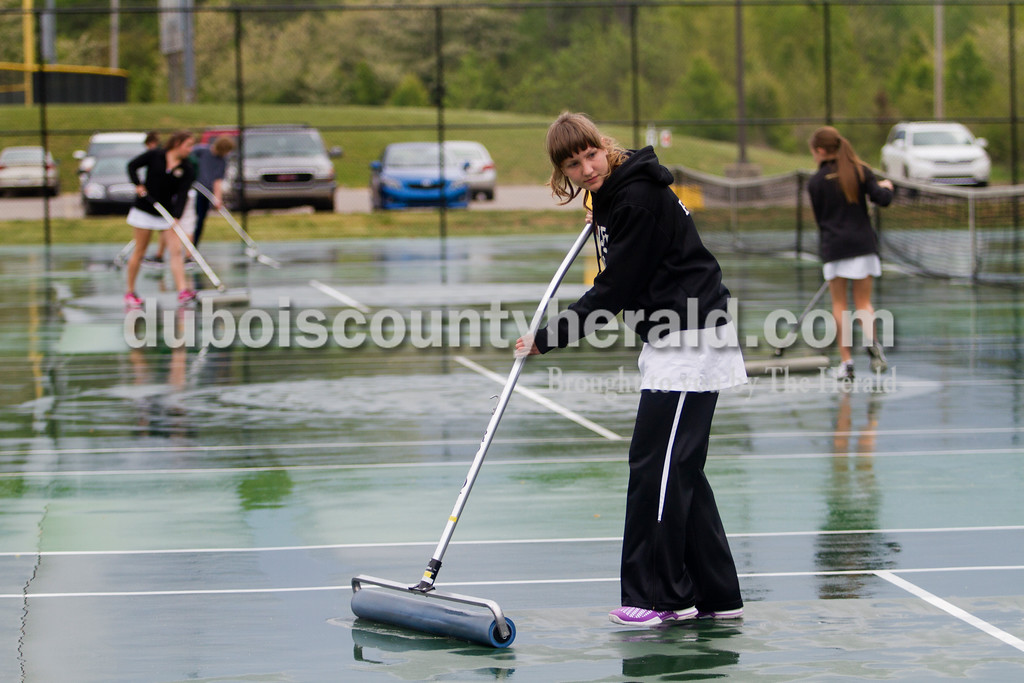 Brooke Stevens/The Herald<br /> Jasper tennis manager Kendra Egler helped dry the courts after a downpour during Saturdays tennis invitational hosted by Jasper.