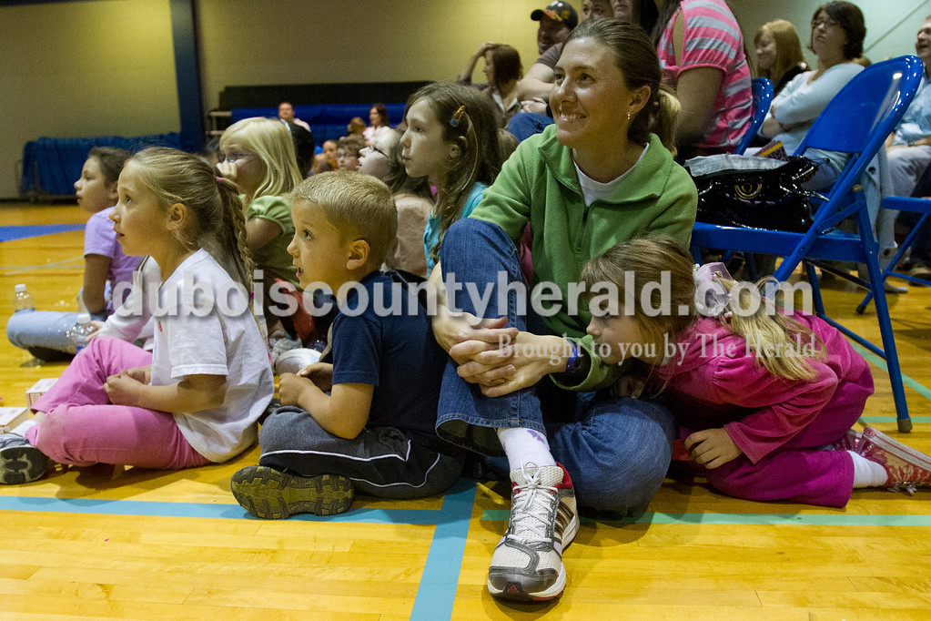 Brooke Stevens/The Herald <br /> Audience members, from left, Emma Tretter, 8, and brother Nigel, 5, of Celestine, and Erin Tower and daughter Abby, 5, of Dubois watched Michael DuBois' Solo Circus Friday night at the Vincennes University Jasper Campus Ruxer Student Center Gymnasium. DuBois performed magic tricks, juggled, and did tricks on a unicycle for the crowd.The event was organized as a family night for students with children and was also opened to the community.