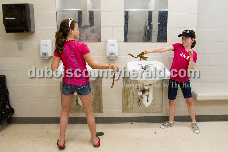 Brooke Stevens/The Herald<br /> Grace Colvin, left, 10, and Heather Gudorf, 10, both of Jasper, cooled off in the women's restroom by slinging wet paper towels at each other before the start of the Forest Park versus Jasper game at Jasper.