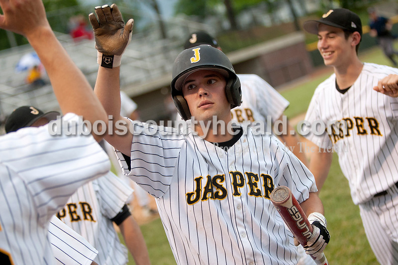 Jasper's Andrew Bies was greeted by teammates after scoring a run during Thursday's game against Gibson Southern at Ruxer Field in Jasper. The Wildcats won 9-8. Dave Weatherwax/The Herald