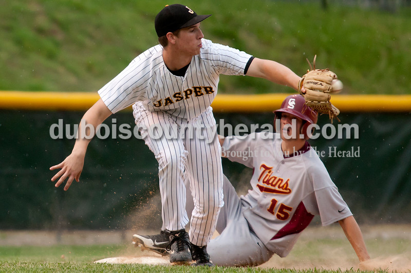 Jasper third baseman Dane Giesler fielded a throw to third but not in time to catch Gibson Southern's Brooks Martin during Thursday's game at Ruxer Field in Jasper. The Wildcats won 9-8. Dave Weatherwax/The Herald
