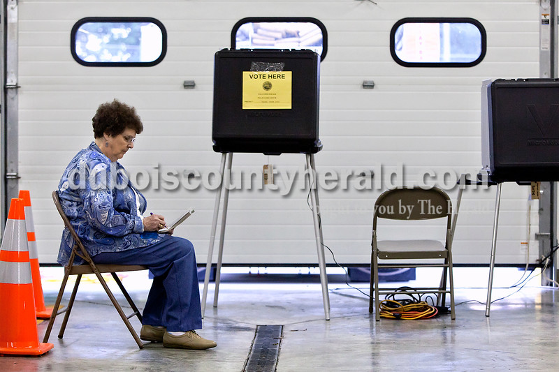 Dave Weatherwax/The Herald<br /> Rita Sendelweck of Ireland worked on a crossword puzzle to pass the time while waiting for voters in the Madison-Jasper North precinct at the Ireland Fire Station this morning. Sendelweck said she was told to bring books to help pass the time but said she wished she had only brought a recliner as well.
