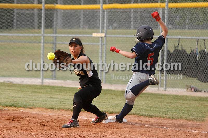 Rachel Mummey/The Herald<br /> The softball reached Jasper's Taylor Main a moment too late as Heritage Hills' Savannah Mundy made it safely to first base during their game in Washington on Monday evening. Heritage Hills won 3-0.