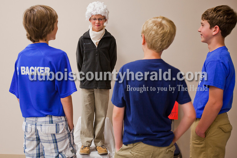 Rachel Mummey/The Herald<br /> Holy Family third grader Sam Greener, of Jasper, dressed as Thomas Jefferson tried not to giggle as sixth graders Chris Backer, Evan Gress,  and Sam Dewitt of Jasper waited to hear Greener's presentation on Thomas Jefferson during Mrs. Giesler's class presentation of a wax museum of past presidents at Holy Family Elementary School on Friday afternoon.
