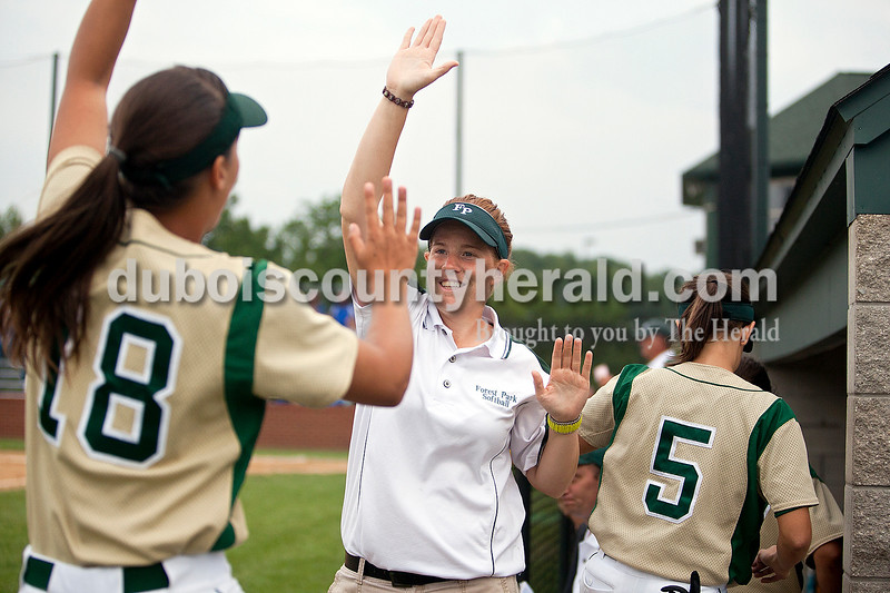 Forest Park's assistant coach Kelly Schroering greeted Jordan Voges, left, and Katelyn Roos after they sprinted to the fence and back in the third inning of Monday night's Class 2A softball sectional in Bretzville. The Rangers lost 3-0. Krista Hall/The Herald