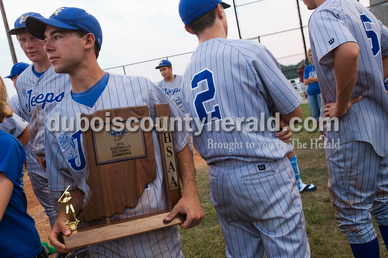 Rachel Mummey/The Herald<br /> Northeast Dubois' Austin Kunz held the sectional trophy with his teammates Jace Gordon, left, and William Schepers, right, Josh Bredhold, background, and Cameron Riecker, far right, after Monday's Class 1A Sectional Championship in Dubois. Dubois defeated Crothersville 13-3.