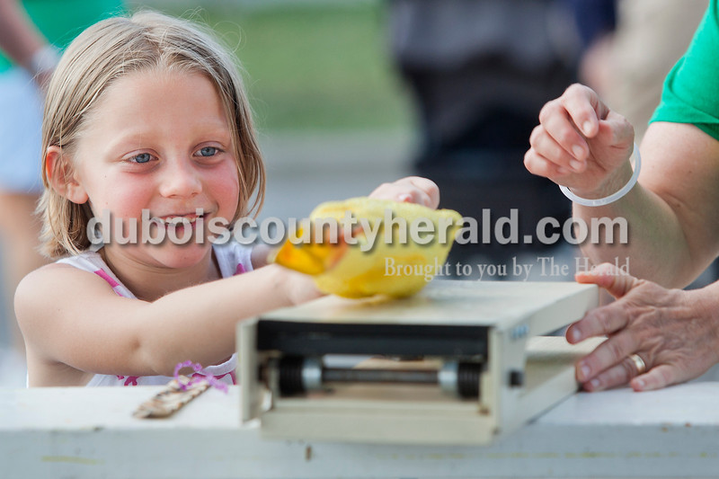 Rachel Mummey/The Herald<br /> Kaitlyn Seffernick of Ferdinand, 7, balanced a rubber chicken on a launching pad at a game stand sponsored by the Sisters of St. Benedict at the Heimatfest in Ferdinand on Friday evening. Seffernick's mother, Angi Seffernick, was the head of this year's Heimatfest committee.