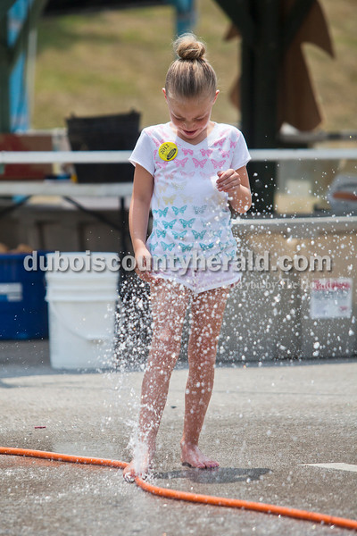 Rachel Mummey/The Herald<br /> Amy Wahl of Ferdinand, 8, found relief from the heat through a hole in the hose near the food stands at the Heimatfest in Ferdinand on Saturday. High temperatures left attendees looking for easy ways to cool off.
