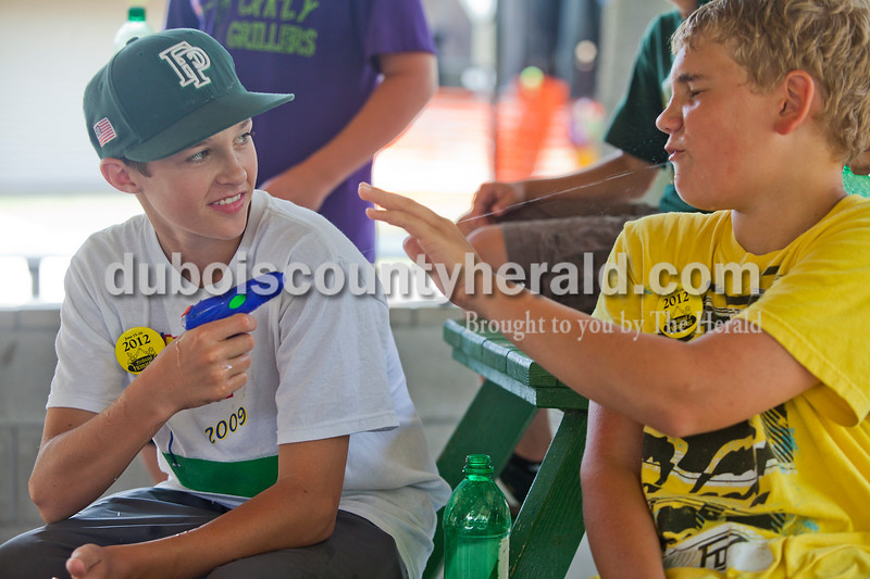 Rachel Mummey/The Herald<br /> Reid Brown of Ferdinand, 13, squirt Levi Hoffman of Huntingburg, 13, in the face with a squirt gun during the Heimatfest in Ferdinand on Saturday. High temperatures left attendees looking for ways to cool off.