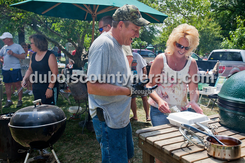 Rachel Mummey/The Herald<br /> Ben Kitten of Ferdinand and Connie Wendholt of Ferdinand shared a laugh as they prepared their barbecue entry for the judges during the backyard barbecue contest during the Heimatfest in Ferdinand on Saturday. The contest judged chicken, beef, pulled pork, and pork ribs.