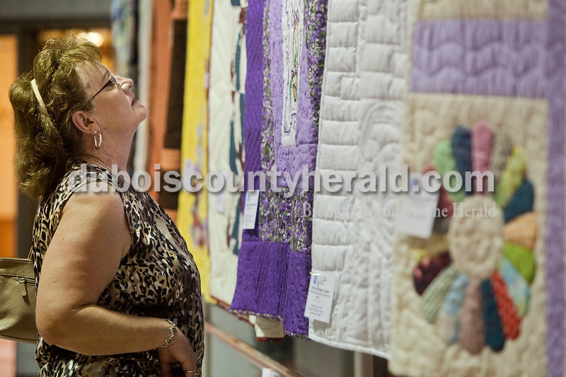 Rachel Mummey/The Herald<br /> Kathy Kluemper of Bretzville looked at quilts at the quilt show in the Ferdinand Community Center during the Heimatfest on Saturday afternoon. The quilts were on display to promote the Sister of St. Benedict's summer social which is scheduled for July 7 in Ferdinand.