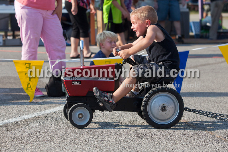 Rachel Mummey/The Herald<br /> Grant Fleck of Ferdinand, 5, laughed as he peddled his way to the finish line during the kiddie tractor pull at the Heimatfest in Ferdinand on Saturday. There were 49 kids who participated in the tractor pull.