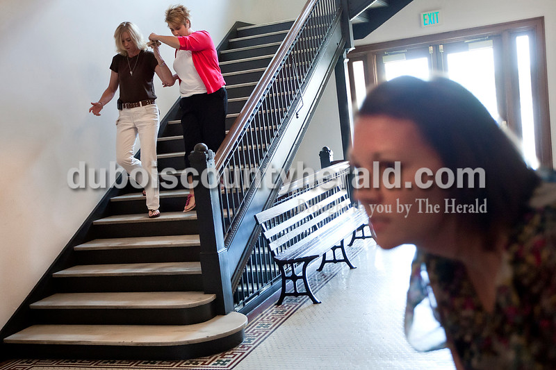 """While playing the role of a """"wounded citizen,"""" the County Emergency Management Agency Director Tammy Miller, left, was assisted by probation assistant Angie Hulsman while work release case manager Jenny Fuhs kept a lookout for the shooter during a training scenario at the Dubois County Courthouse on Tuesday."""