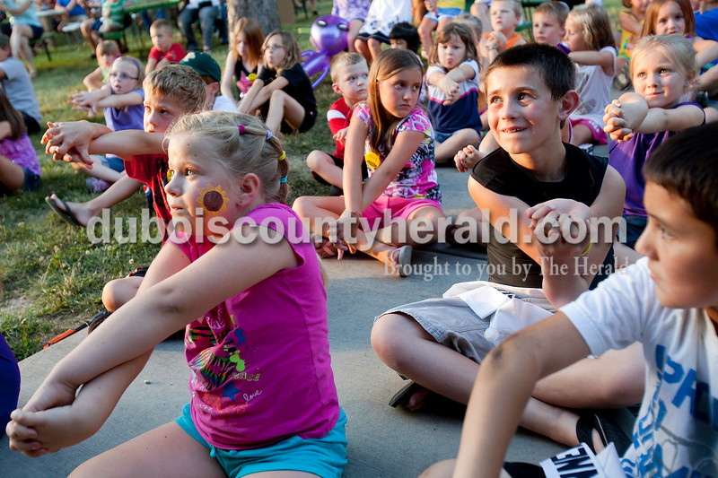 Rachel Mummey/The Herald<br /> Ava Widolff of Ferdinand, 8, foreground left, Ethan Hassfurther of Ferdinand, 8, and Kaden Bowman of Ferdinand, 8, right, twisted their arms as instructed during the Magic with Style show at the Heimatfest celebration on Friday evening. Ethan was this years Little Mister Heimatfest and Kaden was the runner up.