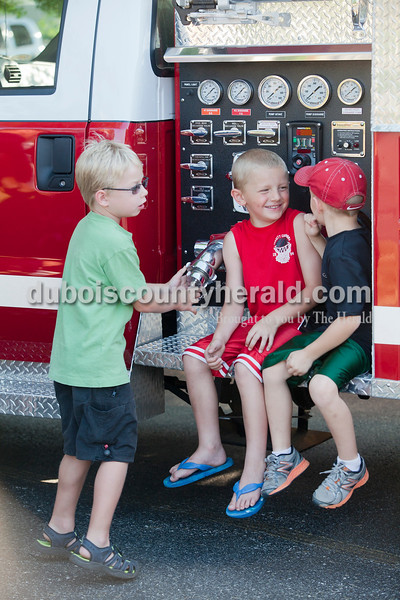 Rachel Mummey/The Herald<br /> Mason Tobin, 6, Carter Giesler, 6, and Elijiah Brosmer, 5, all of Ferdinand, hung out on the firetruck at the waterball competition during the Heimatfest in Ferdinand on Friday evening. All of the boys' fathers, Mike Tobin, Brett Giesler, and Scott Brosmer, all of Ferdinand, are members of the volunteer fire department and participated in the competition.