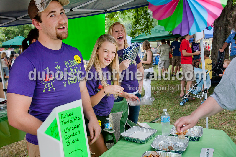 """Rachel Mummey/The Herald<br /> Cole Schneider of Evansville got laughed at by his fiancé, Ashley Becher of Ferinand, background, and her sister, Sabrina Becher of Ferdinand 14, for calling out, """"Monkey balls! Sassy sausage!"""" during the taste testing portion of the backyard barbecue contest during the Heimatfest in Ferdinand on Saturday."""