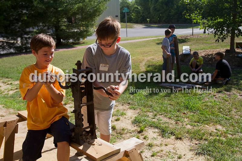 Brooke Stevens/The Herald<br /> Austin Rawlings of Jasper,11, and Jackson Rumfelt of Ireland, 9, drilled a hole into a piece of wood during ArchiCamp at the Schaeffer Barn in Jasper Tuesday morning. Kids ages 8-12 participated in the camp co-sponsored by Indiana Landmarks and Preserve Dubois County. The campers learned about past and present local architecture and building tools.