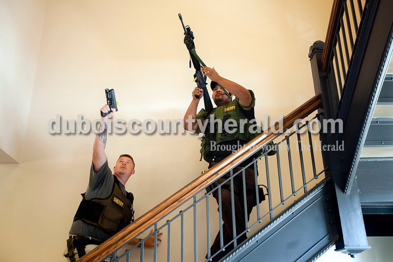 Dave Weatherwax/The Herald<br /> Dubois County Sheriff's Department deputies Chris Faulkenberg, left, and Jesus Monarrez trained their guns up to the second floor as they swiftly moved up the stairs in the Dubois County Courthouse on Tuesday afternoon during a training scenario. The scenario, which was staged by the sheriff's department and incorporated courthouse employees, allowed the deputies to train in quickly securing the building with an active shooter.