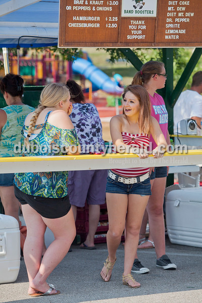 Rachel Mummey/The Herald<br /> Nicole Huff of Schnellville, 16, right, shared a laugh with Tierra O'Keefe of Birdseye, 16, left, while working the food stand for the Forest Park Band Boosters during the Heimatfest in Ferdinand on Saturday. Also working the booth was Madison Bayer of Birdseye, 14, and Samantha Welp of St. Anthony, 16.