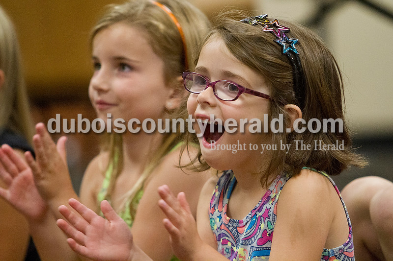 Brooke Stevens/The Herald<br /> Chloe Beck, 6, and Romey Werner, 5, both of Jasper watched Jasper High School cheerleaders demonstrate stunts during Girls Night Out, a fundraiser for the cheerleaders Friday night. Around 30 elementary school aged girls participated in the fundraiser where they learned cheers, ate pizza, watched a move and had their hair styled by the cheerleaders.