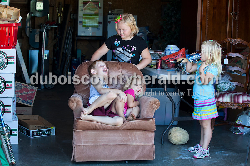 Rachel Mummey/The Herald<br /> Maddox Schnell of Celestine, 7, squealed with joy with his sister Kinley, 2, as they were spun by older sister Corbyn, 8, while sister Raynie, 4, paused for a drink in their grandpa's garage in Jasper on Tuesday morning. Their grandpa, Tony Merder of Jasper, has sold produce from Gibson County out of his home on Mill Street for the past three years.