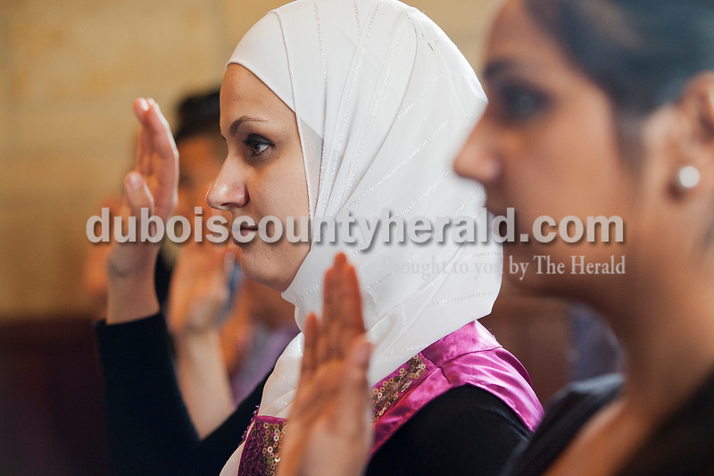 Rachel Mummey/The Herald<br /> Sawsan Rashdan of Indianapolis held up her hand to take her oath during the naturalization ceremony at the Lincoln Boyhood National Memorial on Tuesday. Rashdan is originally from Syria. Seventy-five individuals became citizens at the ceremony.