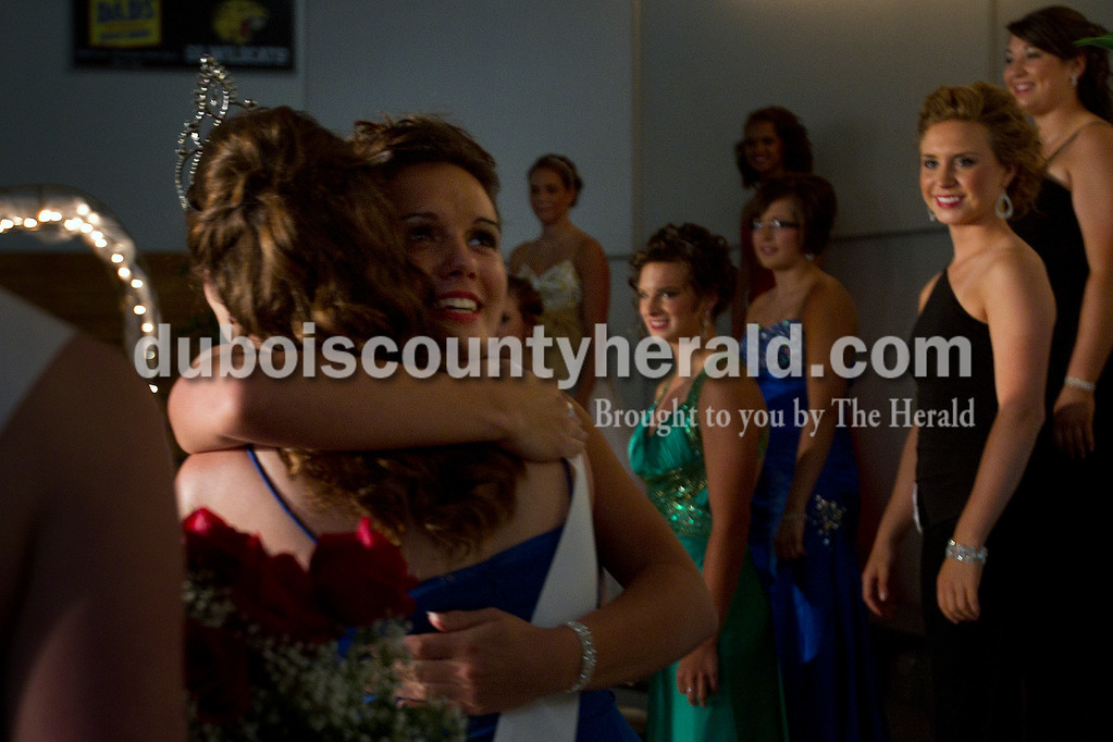 Olivia Corya/The Herald<br /> 2012 Dubois County 4-H Fair Queen Rhegann B. Fetter of Huntingburg, 18, hugged 2011 Queen Kaitlin Emmert of Ferdinand after being announced the winner as Mekenna Knies of Celestine, 18, second to left in front row, and Amanda Gress of Celestine, 18, far right watched at Jasper Middle School Saturday. Fetter, who plans to attend Rose-Hulman Institute of Technology to study electrical engineering,  will reign over the fair from July 15 to 21.