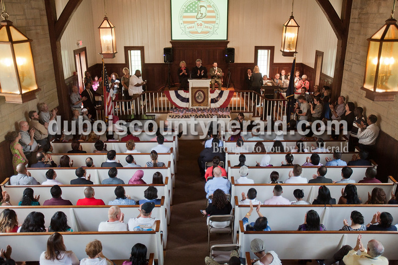 Rachel Mummey/The Herald<br /> The naturalization ceremony at the Lincoln Boyhood National Memorial on Tuesday granted citizenship to seventy-five individuals. With their friends and family members attending the room was full past capacity.