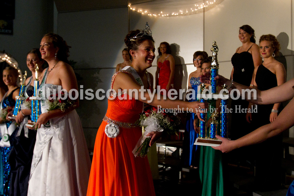 Olivia Corya/The Herald<br /> 2012 Dubois County 4-H Fair Queen Rhegann B. Fetter of Huntingburg, 18, received her trophy from 2011 Queen Kaitlin Emmert of Ferdinand as first runner up Samantha Hopf of Huntingburg, 18, stands in the background left of Fetter after the awards were announced at Jasper Middle School Saturday. Fetter, who plans to attend Rose-Hulman Institute of Technology to study electrical engineering,  will reign over the fair from July 15 to 21.