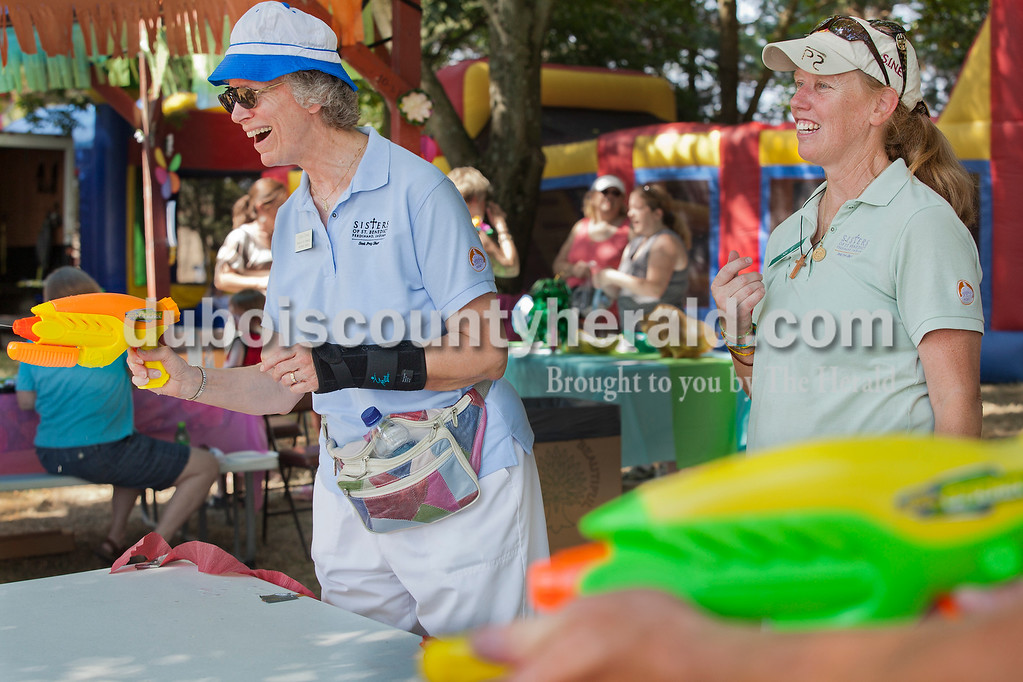 Rachel Mummey/The Herald<br /> Sister Betty Drewes of Ferdinand, left, tried out the squirt gun challenge with Sister Teresa Gunter of Ferdinand at the Sisters of St. Benedict Summer Social on Saturday. In addition to games, there was an art show, a quilt raffle, and guided tours of the monastery.