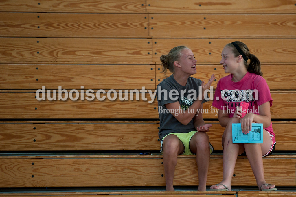 Olivia Corya/The Herald<br /> Madelyn Pund, 12, left, and friend Sara Helming, 12, both of_____, giggled while waiting for the Dubois County 4-H Fair Queen Contest to begin at Jasper Middle School Saturday. Out of fourteen contestants, Rhegann B. Fetter, graduate of Southridge High School, was crowned as Queen.
