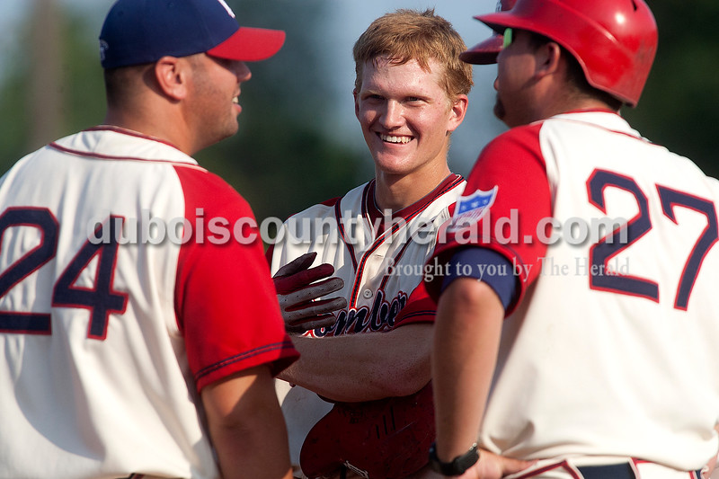 Dubois County Bombers' Jeff Zahn, middle, shared a laugh with coaches Ryan Anderson, left, and Jordan Keener, right, during the first game in the doubleheader against the Quincy Gems on Monday at League Stadium in Huntingburg. Dave Weatherwax/The Herald