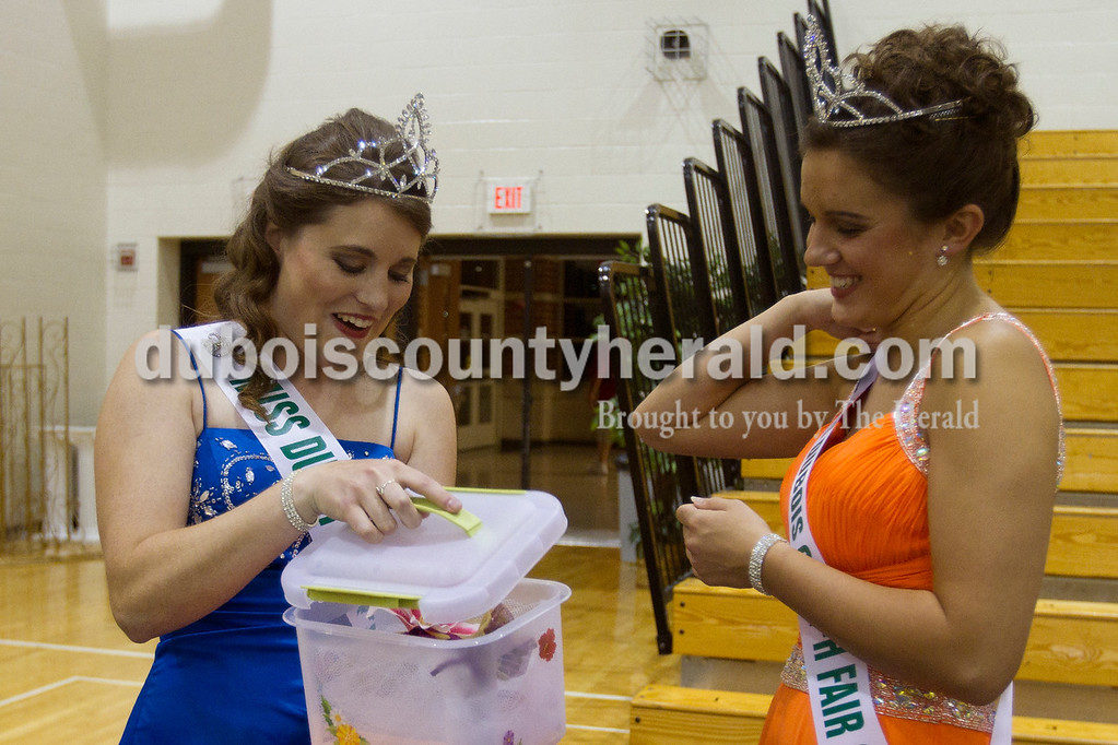 """Olivia Corya/The Herald<br /> 2011 Dubois County 4-H Fair Queen Kaitlin Emmert of Ferdinand, left, gives a crown box to 2011 Queen Rhegann B. Fetter of Huntingburg, 18, after the competition Jasper Middle School Saturday. Among other small surprises in the box, Emmert included a picture frame saying """"Queen"""" that she found on vacation and a charm bracelet to which every queen adds a charm."""
