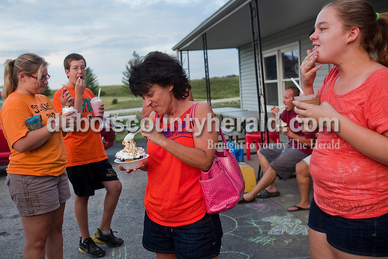 Rachel Mummey/The Herald<br /> Karla Leinenbach of Jasper, center, dug into her ice cream sundae with Megan Knust of Jasper, far left, and her children, Blake Leinenbach, 14, second from left, and Amber Leinenbach, 12, right, at the Windmill Chill on Saturday evening. The family, along with members of the Antley family of Jasper, said usually fourteen of them go down to Holland for ice cream together on Saturday nights as a family get together.