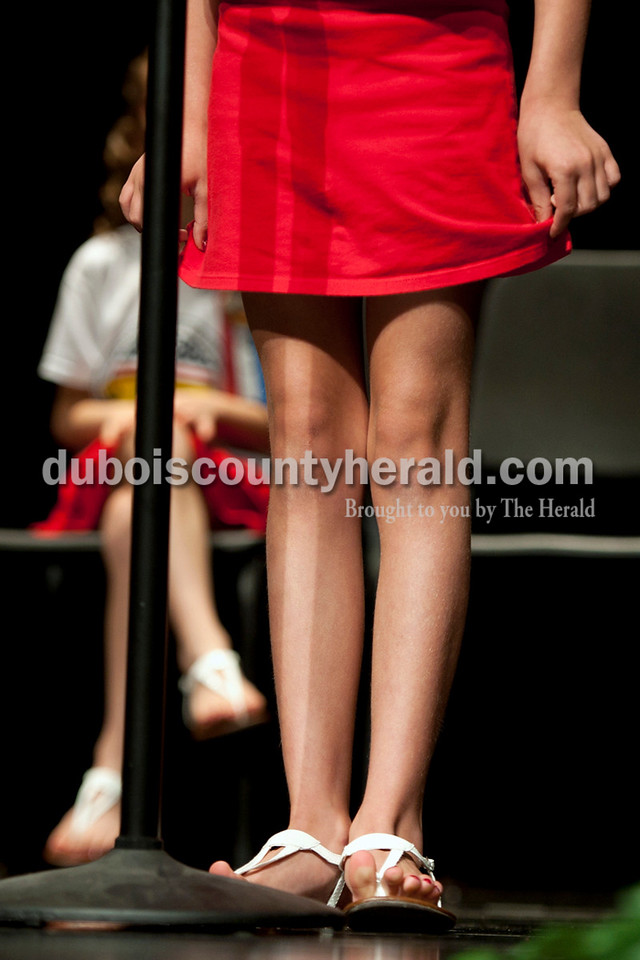 Olivia Corya/The Herald<br /> 2012 Little Miss Strassenfest contestant Tori Brandt of Jasper, 7, fidgeted with her skirt as she answered interview questions in front of a panel of judges and the audience at the Jasper Middle School Saturday. The contestants for the Little Miss and Little Mister pageant were asked about their parents' names, pets, favorite school subjects, and hobbies.