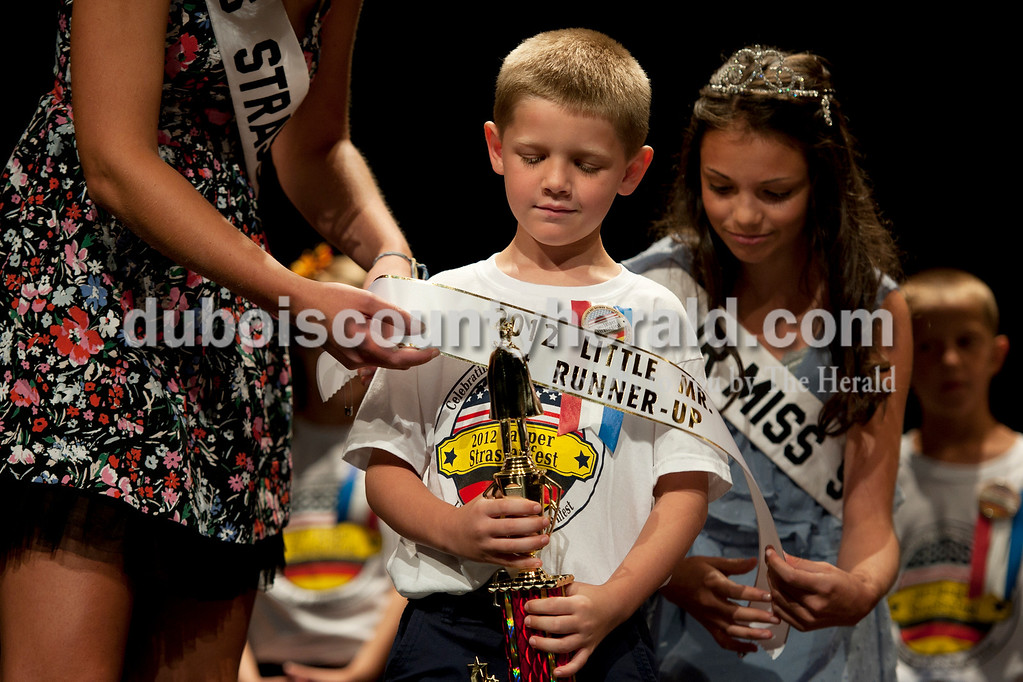 Olivia Corya/The Herald<br /> 2012 Little Mister Strassenfest first runner-up Tommy Gilbert of Jasper, 7, smiled at his trophy as 2011 Miss Strassenfest Hannah Burgess of Jasper, 20, left, and 2011 Jr. Miss Strassenfest Chloe Smith of Jasper, 12, put on his sash at the Jasper Middle School Saturday.