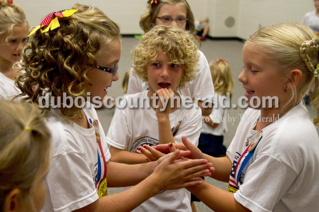 Olivia Corya/The Herald<br /> Little Miss Strassenfest contestants Brianna Williams of Jasper, 7, left, and Addison Hildenbrand of Jasper, 8, right, played a hand game together as Kanon Schnarr of Jasper, 7, watched while waiting for the pageant to begin at the Jasper Middle School Saturday.