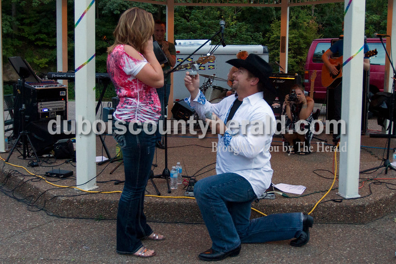"""Olivia Corya/The Herald<br /> Mark Schneider proposed to Vicky Couch, both of New Salisbury, during a concert of one of their favorite bands, The Hiding, at the Dave Buehler Plaza along the Patoka River on Saturday. Schneider first brought Couch up to the gazebo to dance, then borrowed the mic to sing her """"Woman Like You"""" by Lee Brice, then got down on one knee. She said yes."""