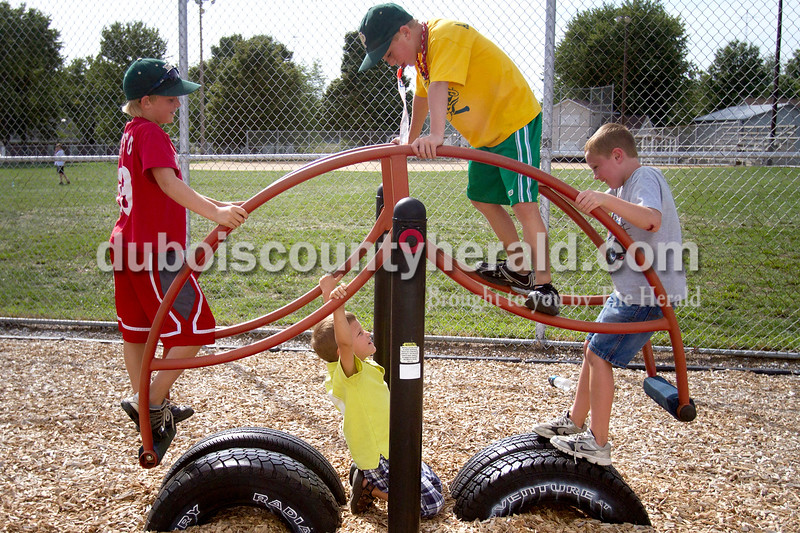 Collin Rothgerber of St. Anthony, 9, from left, Parker Wolf of St. Anthony, 4, Brody Klem of Ferdinand, 8, and Adam Englert of St. Anthony, 8,  entertained themselves on a play set during the St. Anthony Firemen's Fest at the St. Anthony Community Center on Saturday. The annual festival is a fundraiser for St. Anthony Volunteer Fire Department.  Olivia Corya/The Herald