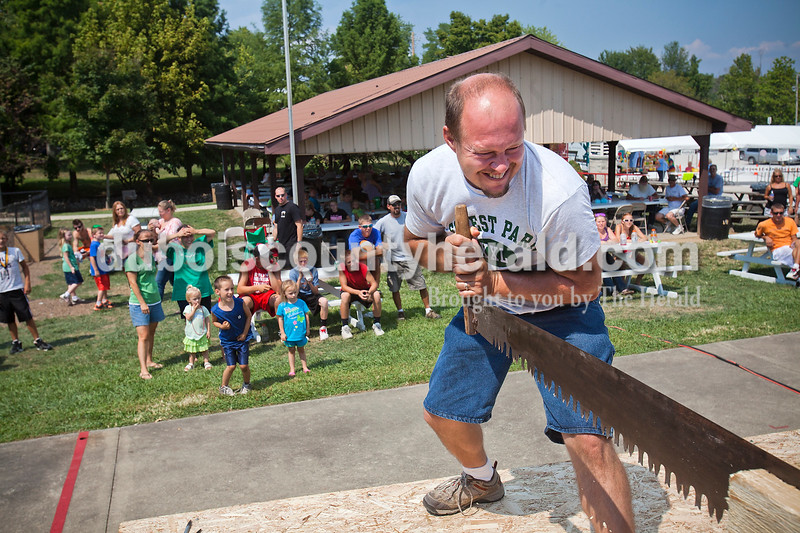 Rachel Mummey/The Herald<br /> Jeremy Uebelhor of Bridseye sawed feverishly with his partner Allen Cooper of Birdseye, not pictured, during the log sawing competition at the Birdseye Picnic on Saturday. The event hosted meals, games, a car show, basketball tournament and live music.