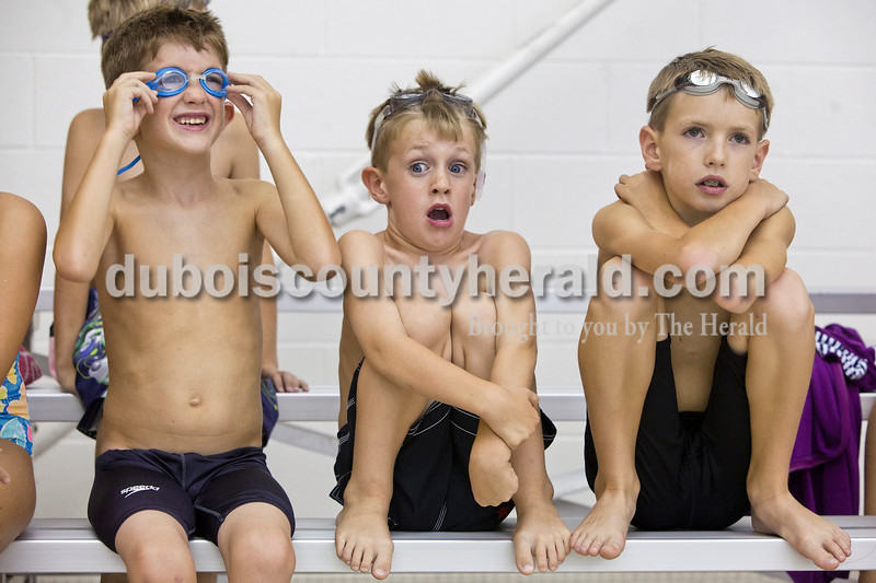 Rachel Mummey/The Herald<br /> Leo Eckman of Jasper, 6, left, adjusted his goggles while his younger brother Wes, 5, center, gasped as a swimmer jumping into the pool, next to his older brother Abe, 8, right, who calmly waited for the Jasper Aquatic Wildcats Swim Camp to begin at Jasper High School Natatorium on Monday. The swim camp, which lasts one week, allows less experienced swimmers a taste of what it is like to a part of JAWS, which begins its season Sept. 4.